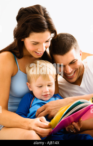 Caucasian parents and toddler son reading book - Stock Photo