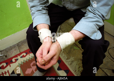Man with deep depression and bandaged wrists from suicide attempt. - Stock Photo