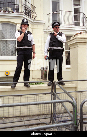 Two police officers standing on a wall on guard watching a demonstration pass by. - Stock Photo