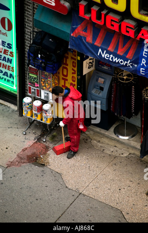 City worker cleans debris and litter from Midtown Manhattan sidewalk with broom and dustpan New York NY - Stock Photo