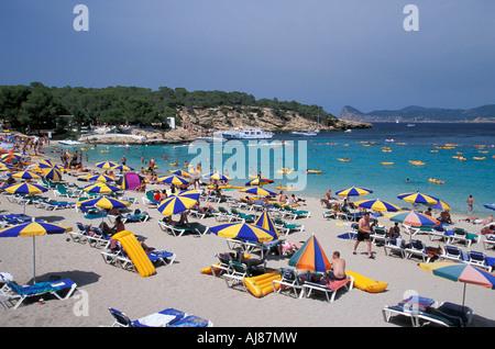 People relaxing at beach Cala Bassa San Antonio Ibiza Balearic Islands Spain - Stock Photo