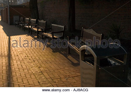 A row of empty wooden benches, and a stainless steel waste bin, in sunshine and shade - Stock Photo
