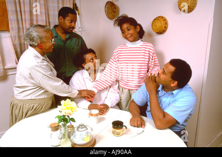 Extended African American family consoling 13 year old in the kitchen. St Paul Minnesota USA - Stock Photo