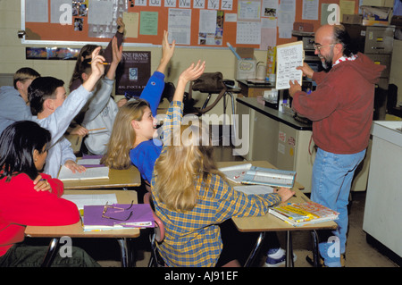 Students age 14 with hands raised reciting Spanish with teacher. Golden Valley Minnesota USA - Stock Photo
