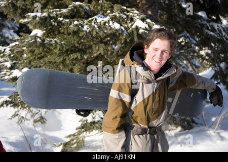 Young man with snowboard in backcountry - Stock Photo