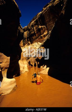 Wading through water in desert canyon - Stock Photo