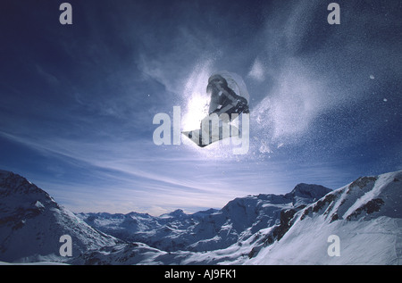 Snowboarder flies into the sun in Les Arcs French Alps - Stock Photo