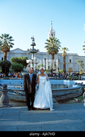 Newly married couple in front of Tuturutu Fountain and Cathedral, Plaza de Armas, Arequipa, Peru - Stock Photo