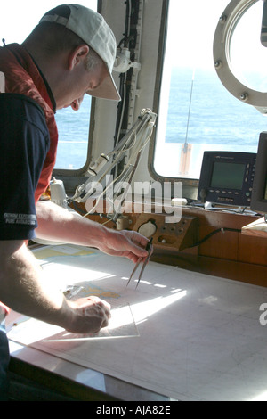 Navigator standing over charts working out the ships course - Stock Photo