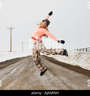 Young woman in winter clothes standing on muddy dirt road jumping and smiling - Stock Photo