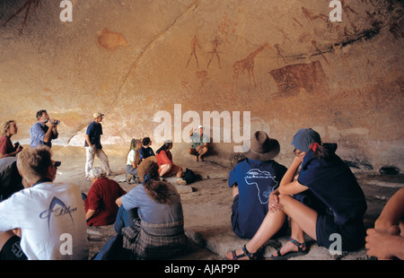 Guide Ian Harmer gives lecture on Bushman paintings inside a cave in Matobo National Park Zimbabwe - Stock Photo