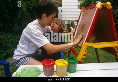 An infant looks into her mother's face while painting art with her mum on an easel in their back garden in South - Stock Photo