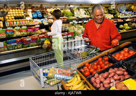 Middle aged African American man and woman in grocery store shopping for produce - Stock Photo