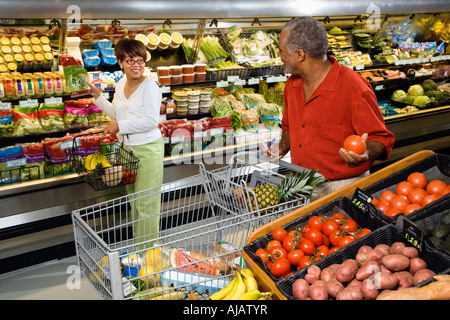 Middle aged African American woman pointing out produce in grocery store to middle aged man - Stock Photo