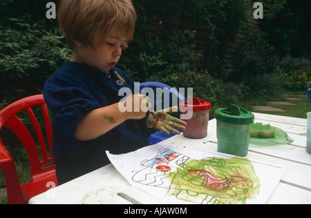 An young infant girl paints her own hand red as she plays with water paints in her back garden London - Stock Photo