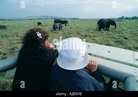 Tourists enjoying a panoramic view of elephants in the Masai Mara National Reserve Kenya East Africa - Stock Photo