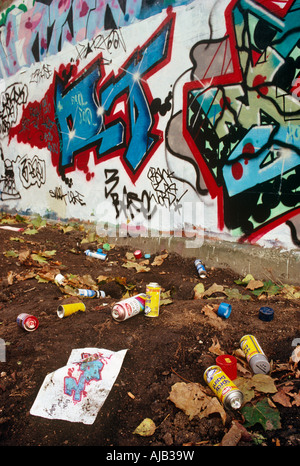 Abandoned aerosol spray cans lie in soil after a graffiti gang's overnight vandalism visit in Notting Hill West - Stock Photo