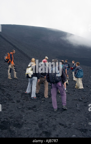 Hikers near the Smoke and steam emitted from Torre di Filosofo at 2920 meters erupted 2003 on the Southern slopes - Stock Photo