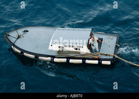 The mooring man boat takes he ropes from the docking vessel to be tied to the wharf port of Messina Sicily Italy - Stock Photo