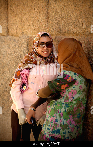 Two modern stylishly dressed Egyptian young women with headscarves in Khafre s Valley Temple Giza Cairo Egypt Africa - Stock Photo