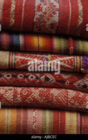 A stack of Peruvian and Bolivian woven woollen textiles as sold in La Paz Bolivia Cuzco and Pisac Peru - Stock Photo