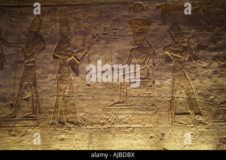 carving of Queen Nefertari offering lotus flowers to Ankuis goddess of Aswan in the small Temple of Abu Simbel Upper - Stock Photo