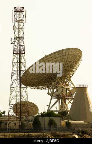 Satellite earth station in Bahrain showing huge satellite dish and microwave dish tower as a communications mast - Stock Photo