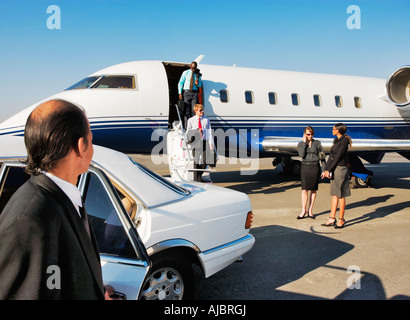 Chauffer Waiting at a Limousine for a Group of Business Executives Exiting Private Jet - Stock Photo
