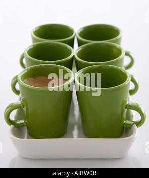 Green Coffee Mugs - One Full - Stock Photo