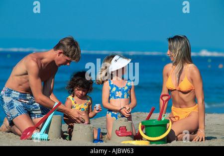 family building sand castle on beach - Stock Photo