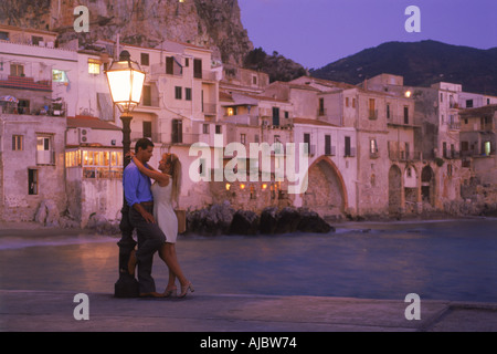 Couple and lamp post on waterfront at sunset in village of Cefalu Sicily - Stock Photo