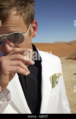 Man in a White Suit with Money in his Pocket, in the Desert - Stock Photo