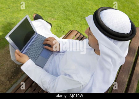 Arab Man Working on Laptop Computer on Bench in Park, High Angle View - Stock Photo