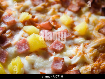 Close up shot of pizzas with cheese and pineapple cooked unitl golden brown often ordered from a take away - Stock Photo