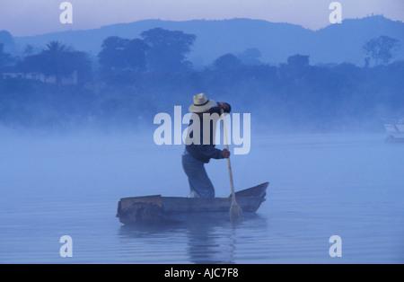 Dredging reeds from a canoe at dawn Santiago Atitlan a Tzutuhil Maya community Lake Atitlan Guatemala - Stock Photo