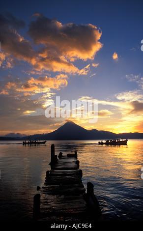 Boats and jetty silhouetted at sunset Panajachel Lake Atitlan Guatemala San Pedro volcano beyond Central America - Stock Photo