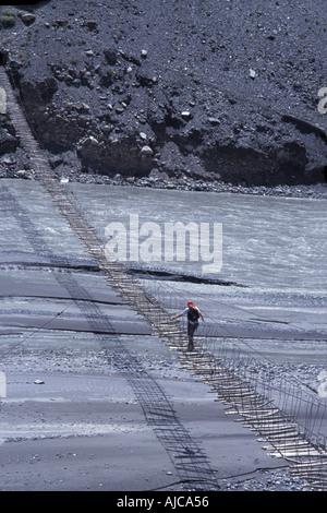 Crossing the Hunza river by way of a suspended footbridge Trekking in and around Passu Karakoram Highway N Pakistan - Stock Photo