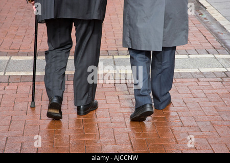 rear view of the legs and feet of two old men walking on cobbled pavement - Stock Photo