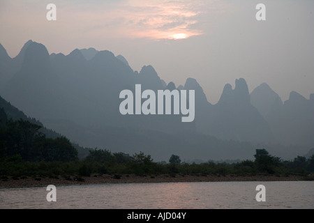 sunset over the mountains on the Li River Guilin China - Stock Photo
