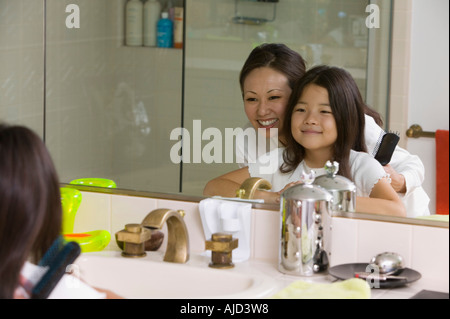 Mother and Daughter Looking at reflection in Bathroom mirror, focus on mirror - Stock Photo