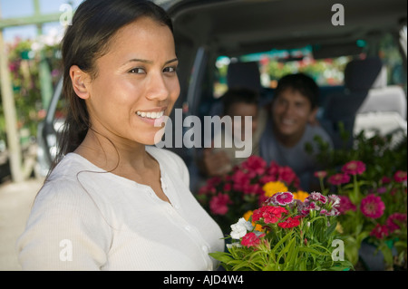 Mother standing by back of minivan holding flowers, portrait - Stock Photo