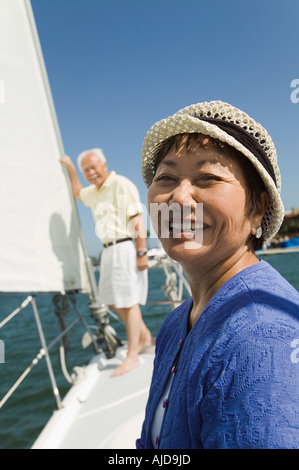 Woman smiling on sailboat, husband in background, (portrait) - Stock Photo