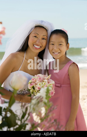 Bride and sister on beach, (portrait) - Stock Photo