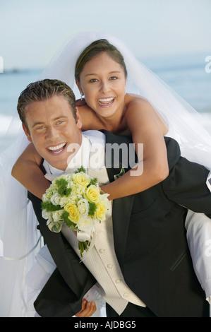 Groom giving Bride piggyback ride, outdoors, (portrait) - Stock Photo