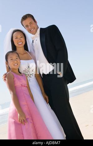 Bride and Groom with sister on beach, (portrait) - Stock Photo