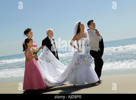 Bride and Groom walking with family on beach - Stock Photo