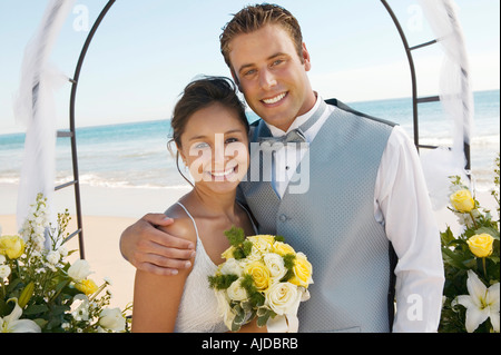 Bride and Groom under archway on beach, (portrait) - Stock Photo