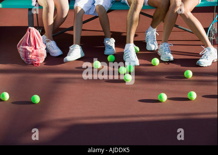 Scattered tennis balls on tennis court by feet of family, low section - Stock Photo