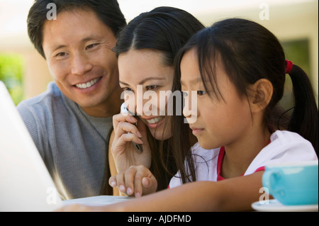 Family Using Laptop in backyard, close up - Stock Photo