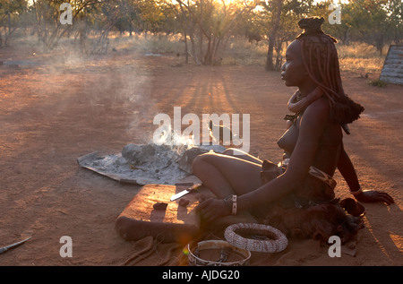 Namibia Kaokoland Himba people Himba women next to her camp fire with chicken covered in Ochre and clay otjize pulverized - Stock Photo